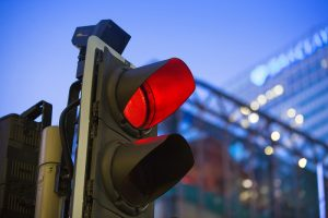 LONDON, UK - 7 SEPTEMBER, 2015: Canary Wharf traffic lights showing red and Barclays bank building on the background